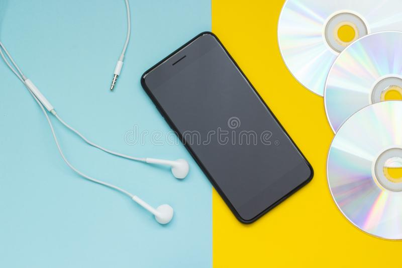 Smartphone con los auriculares y los Cdes en un fondo amarillo azul fotografía de archivo