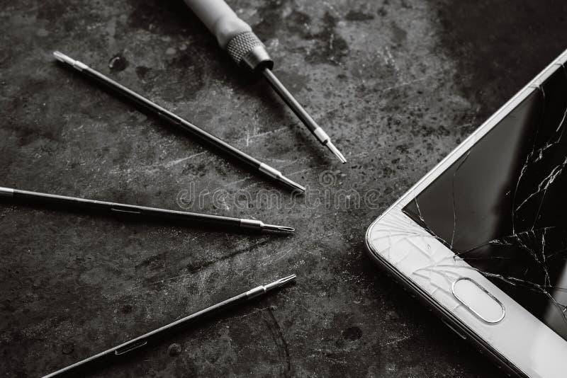 Smartphone con una pantalla quebrada y las herramientas de la reparación fotos de archivo
