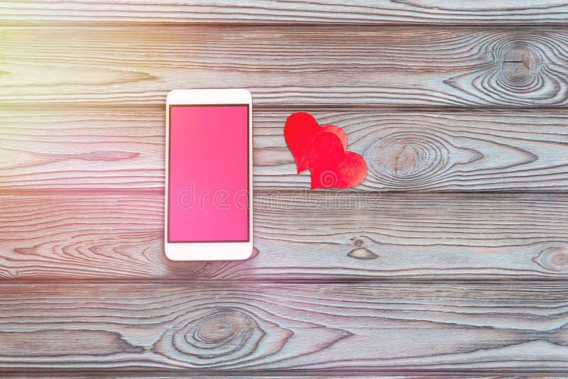Smartphone con una pantalla rosada, una figura en forma de corazón imagen de archivo libre de regalías