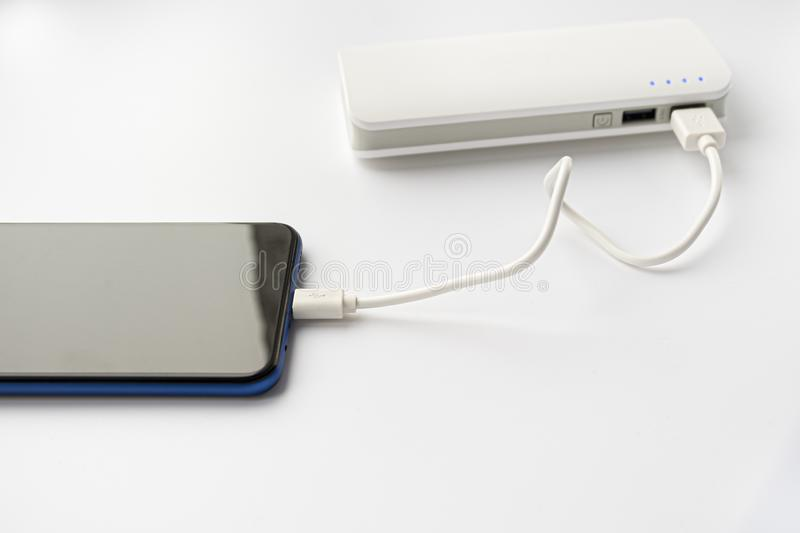 Smartphone connect to power bank. Portable charger on a white background. Charging your phone stock photography