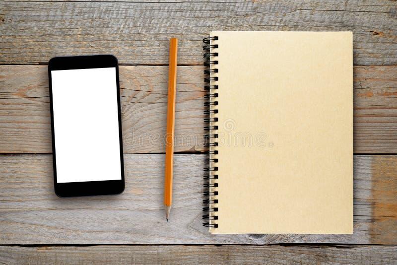 Smartphone, crayon et bloc-notes sur la table photo libre de droits