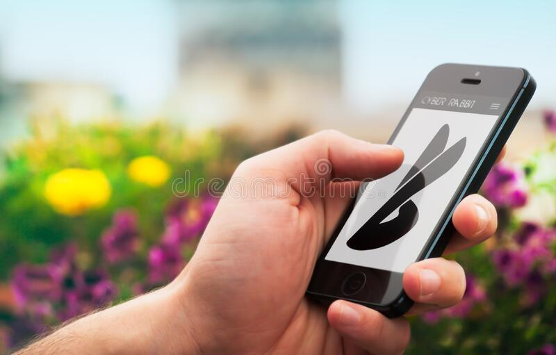 Smartphone εκμετάλλευσης χεριών από το κουνέλι Cyber στοκ εικόνα με δικαίωμα ελεύθερης χρήσης