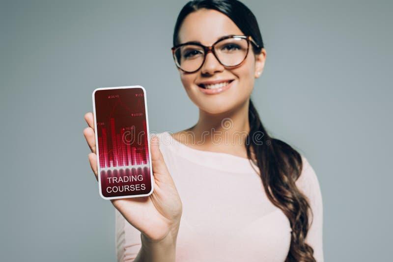 smartphone d'apparence de femme avec des cours de commerce photos libres de droits