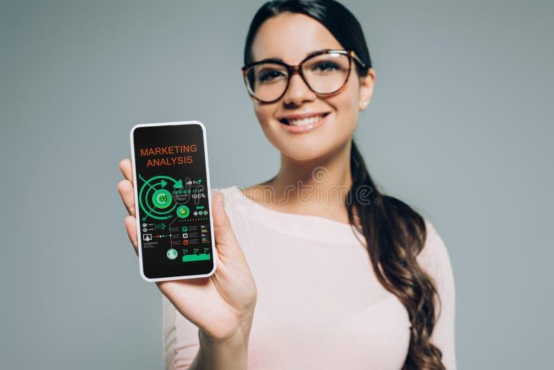 smartphone d'apparence de femme avec l'analyse des marchés et infographic de sourire photographie stock libre de droits