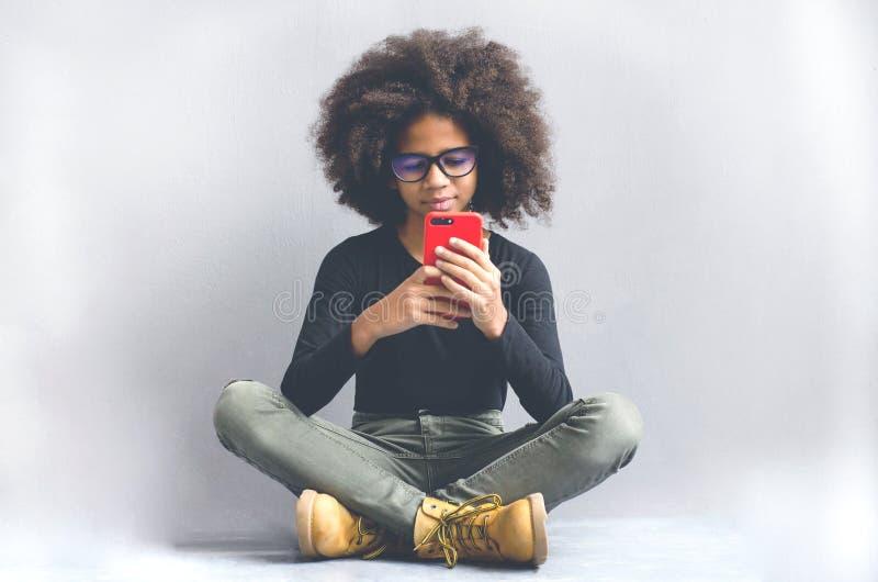 Smartphone d'applauso della ragazza dalla carnagione scura che si siede vicino alla parete fotografie stock