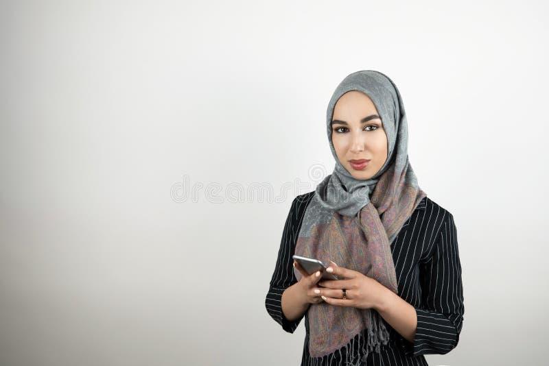 Smartphone d'uso della tenuta del foulard del hijab del turbante della giovane donna musulmana attraente nel suo fondo bianco iso immagini stock libere da diritti