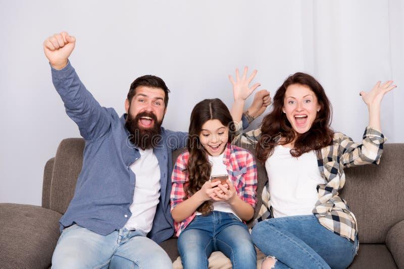 Smartphone d'utilisation de petite fille d'enfant avec des parents Famille amicale ayant l'amusement ensemble Papa de maman et dé photo stock