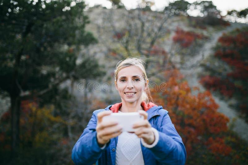 Smartphone d'utilisation de randonneur de femme prenant la photo sur le fond de la montagne et de la forêt photographie stock libre de droits