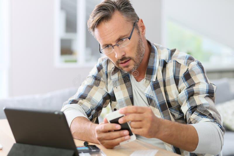 Smartphone da fixação do homem com auxílio do Internet foto de stock royalty free