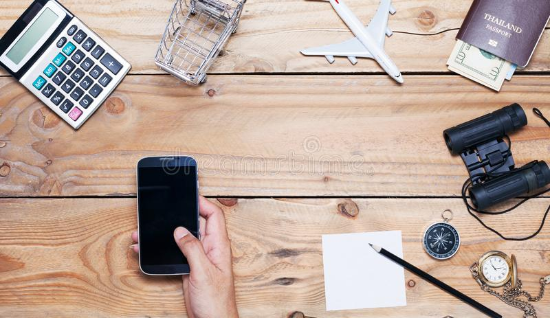 Smartphone da tabuleta do uso do homem da mão com a tabela de madeira da mesa de escritório dos Bu fotos de stock
