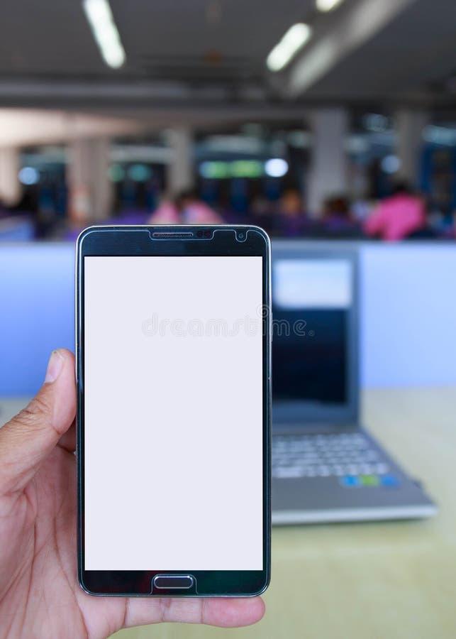 Smartphone da tela vazia nas mãos na biblioteca fotografia de stock royalty free