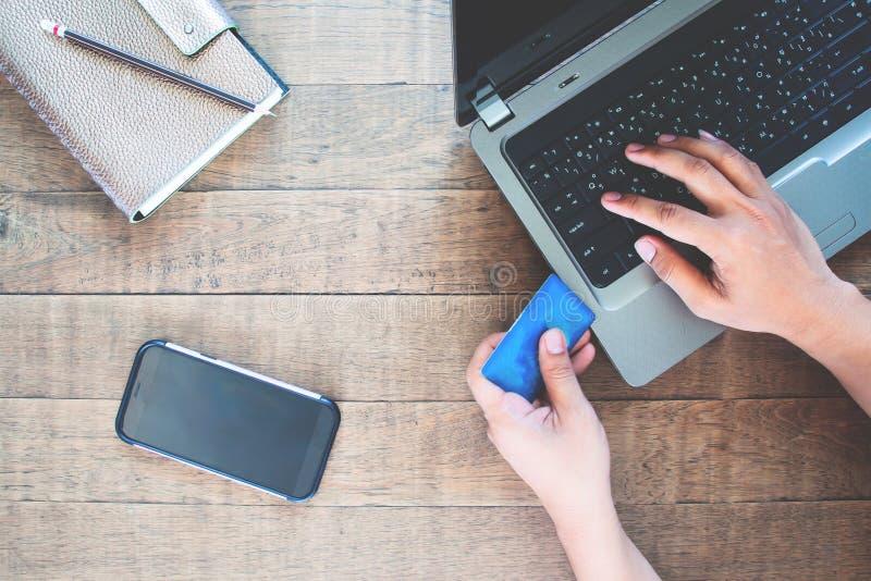 Smartphone da tela vazia para a zombaria da aplicação acima com o homem que usa o cartão e o laptop de crédito foto de stock