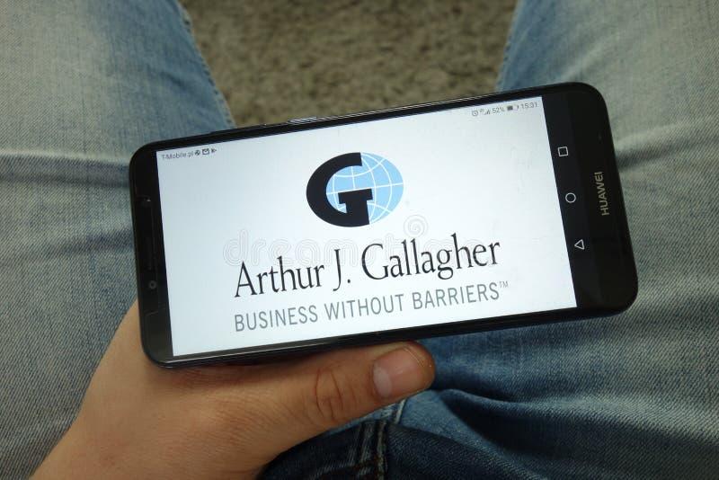 Smartphone da terra arrendada do homem com Arthur J Gallagher & Co logo imagens de stock royalty free