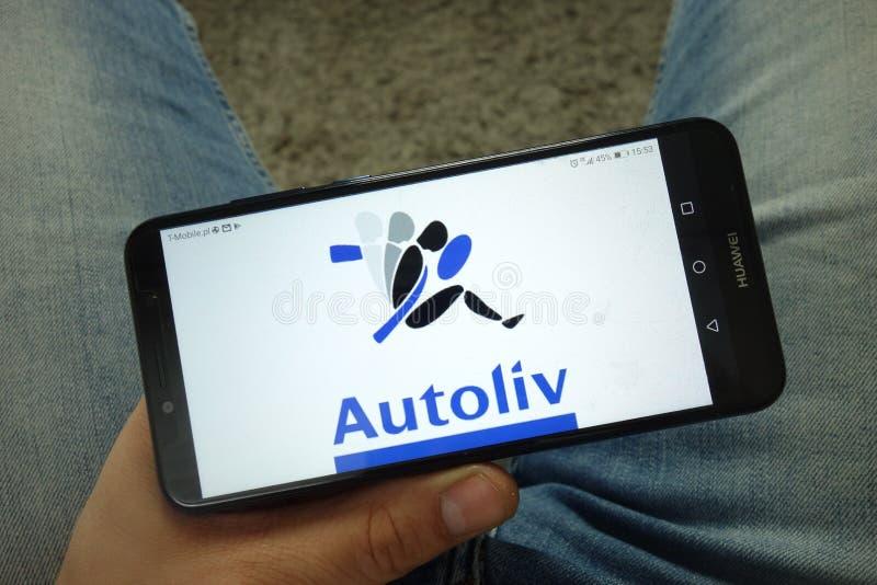 Smartphone da terra arrendada do homem com Autoliv Inc logo fotografia de stock royalty free