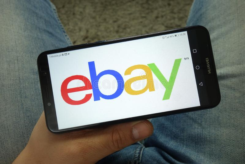 Smartphone da terra arrendada do homem com eBay Inc logo fotografia de stock royalty free