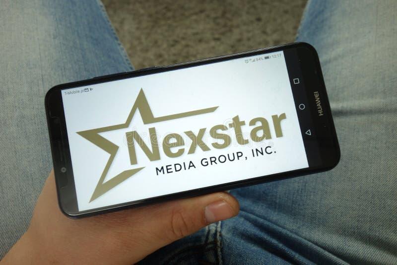 Smartphone da terra arrendada do homem com grupo dos meios de Nexstar, Inc logo fotos de stock royalty free