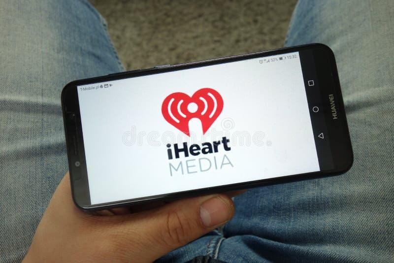 Smartphone da terra arrendada do homem com iHeartMedia, Inc logo foto de stock