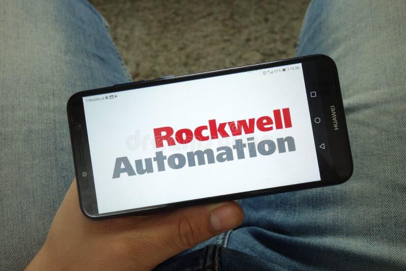Smartphone da terra arrendada do homem com logotipo de Rockwell Automation fotos de stock