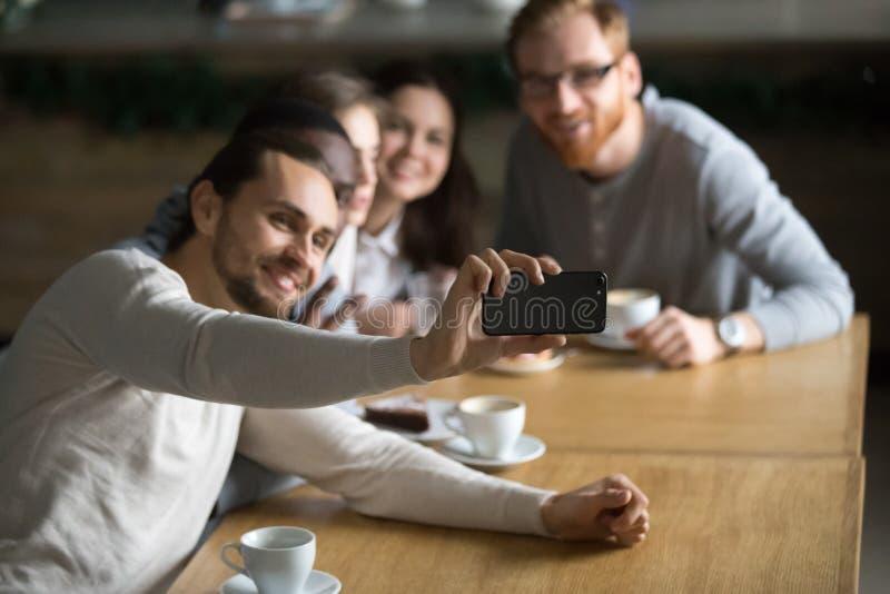 Smartphone da terra arrendada do indivíduo que faz o selfie com amigos foto de stock