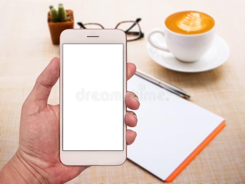Smartphone da terra arrendada da mão do freelancer com a tela branca vazia sobre fotografia de stock royalty free