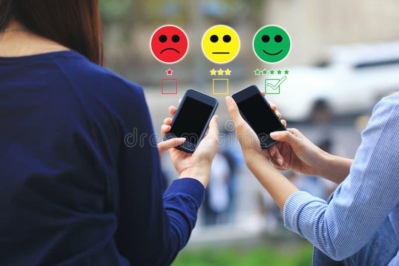 Smartphone da terra arrendada da m?o da jovem mulher e coloca??o identificar de verifica??o por meio do marcador da cara do smile fotos de stock