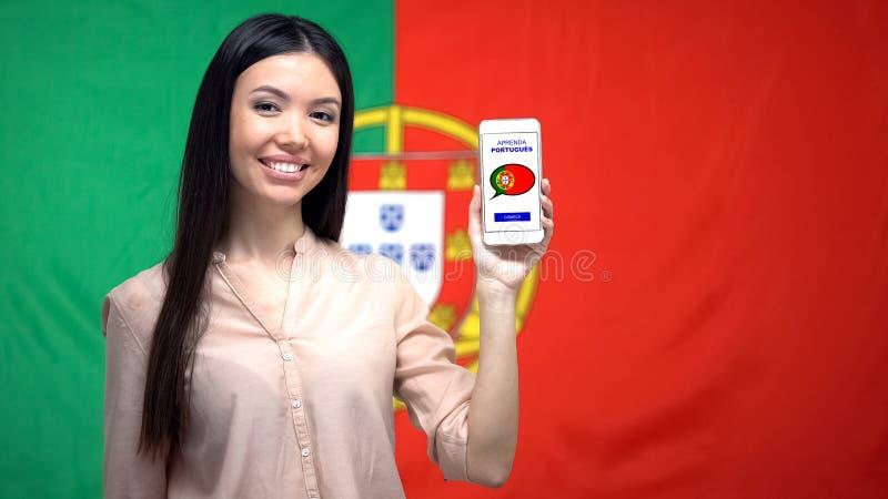 Smartphone da terra arrendada da mulher com o app do estudo da língua, bandeira portuguesa no fundo fotos de stock royalty free