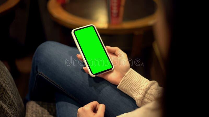 Smartphone da terra arrendada da mulher com tela verde, lugar para o anúncio, molde do canal alfa imagem de stock