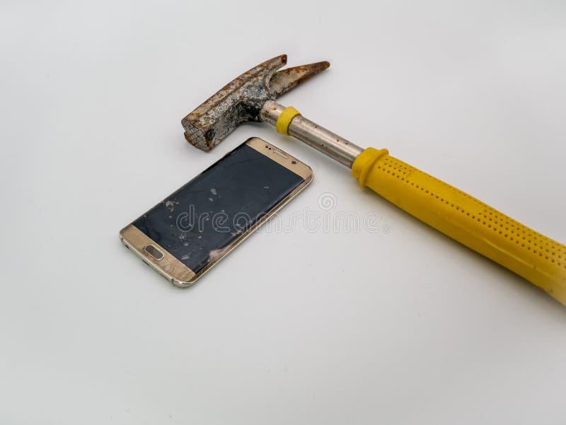 Smartphone danificado disply com martelo e fundo branco imagens de stock