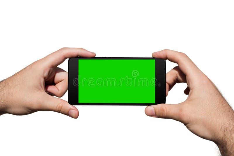 Smartphone dans des mains avec l'écran vert pour l'espace de copie d'isolement sur le fond blanc image libre de droits