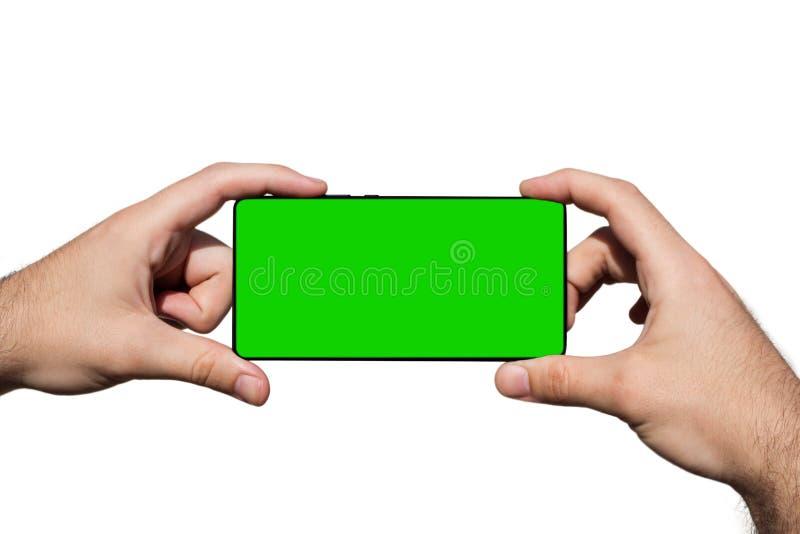 Smartphone dans des mains avec l'écran vert pour l'espace de copie d'isolement sur le fond blanc image stock