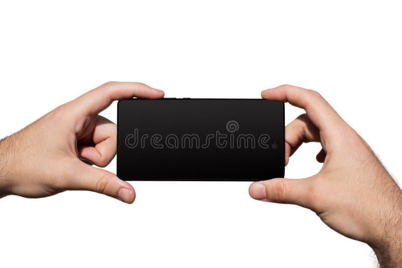 Smartphone dans des mains avec l'écran vide pour l'espace de copie d'isolement sur le fond blanc photographie stock