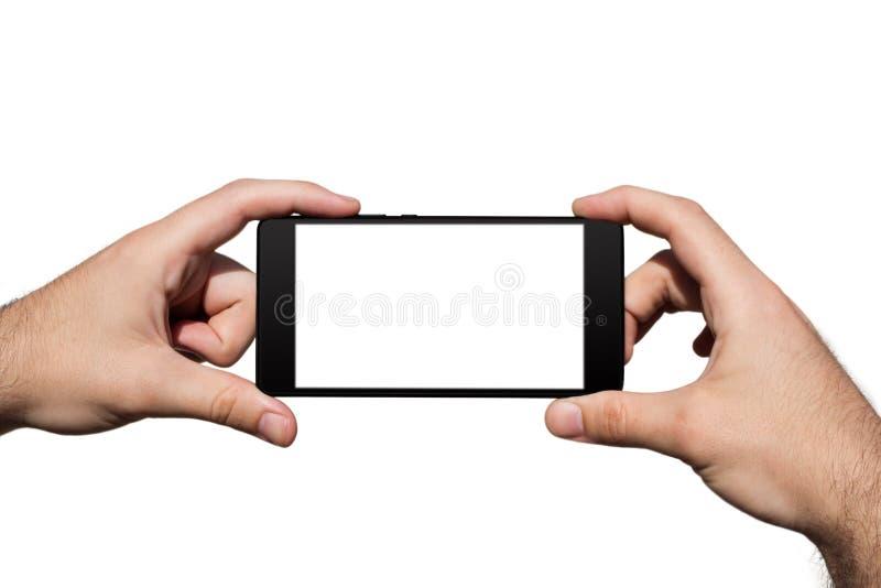 Smartphone dans des mains avec l'écran vide pour l'espace de copie d'isolement sur le fond blanc photo stock