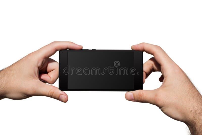 Smartphone dans des mains avec l'écran vide pour l'espace de copie a isolé photographie stock
