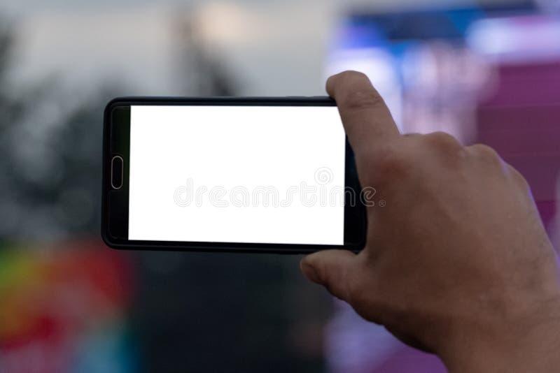 Smartphone dans la main d'un homme Vidéo et photographie à un téléphone portable Écran blanc comme calibre, maquette Blanc pour e photographie stock libre de droits