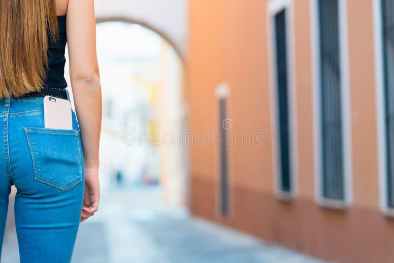 Smartphone dans la poche arrière de jeans Une fille dans des jeans avec un p photos libres de droits