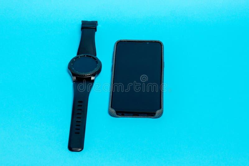 Smartphone dans une caisse grise de textile et une montre intelligente sur un fond bleu Vue sup?rieure photos libres de droits