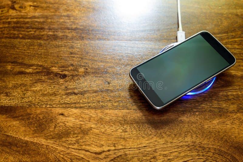 Smartphone, das auf einer Aufladungsauflage auflädt Drahtlose Aufladung stockfoto