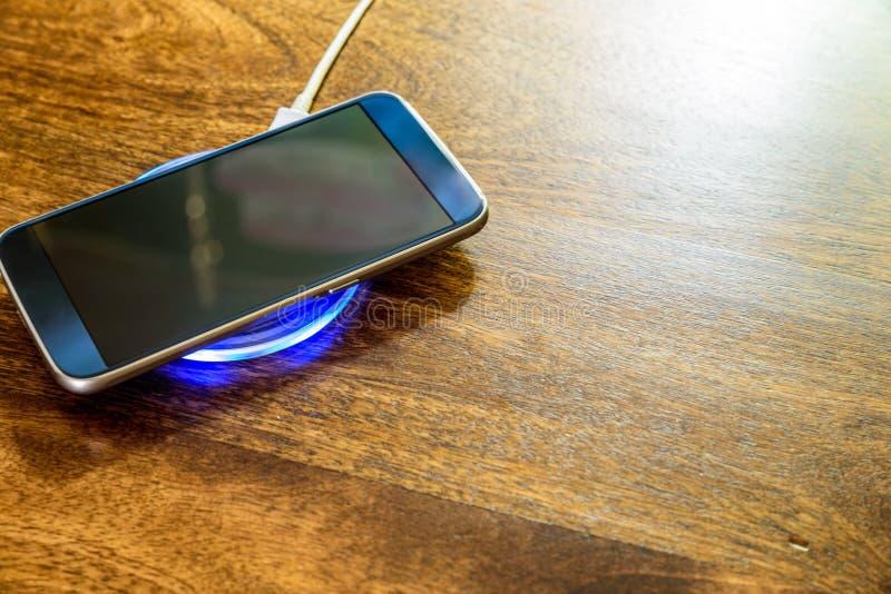 Smartphone, das auf einer Aufladungsauflage auflädt Drahtlose Aufladung stockfotografie