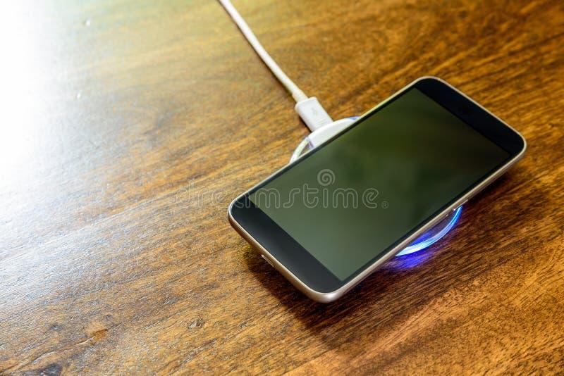 Smartphone, das auf einer Aufladungsauflage auflädt Drahtlose Aufladung lizenzfreie stockfotografie