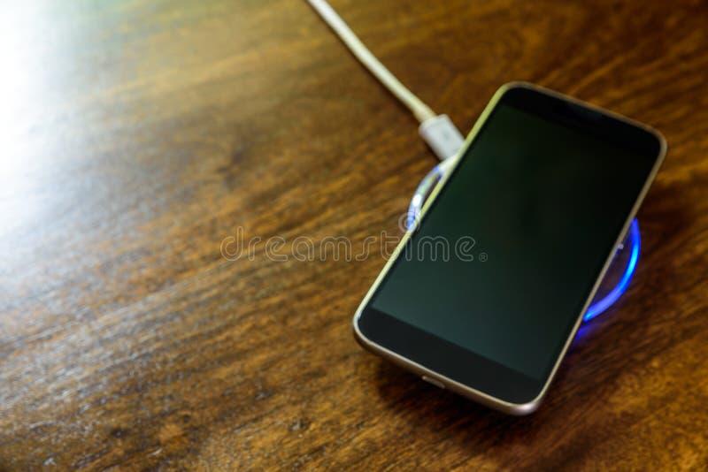 Smartphone, das auf einer Aufladungsauflage auflädt Drahtlose Aufladung stockfotos