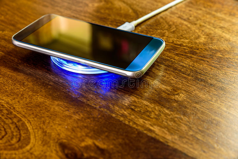 Smartphone, das auf einer Aufladungsauflage auflädt Drahtlose Aufladung lizenzfreie stockbilder