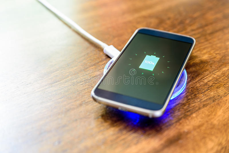 Smartphone, das auf einer Aufladungsauflage auflädt Drahtlose Aufladung lizenzfreies stockbild