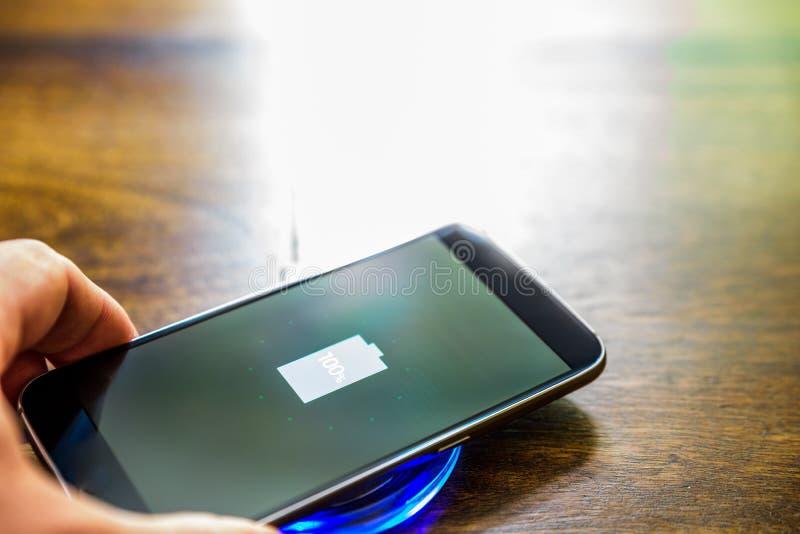 Smartphone, das auf einer Aufladungsauflage auflädt Drahtlose Aufladung lizenzfreie stockfotos
