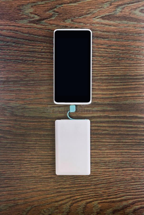 Smartphone, das mit Energiebank auf hölzernem Brett auflädt lizenzfreies stockfoto
