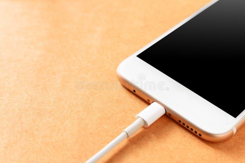 Smartphone, das mit Energiebank auf hölzernem Brett auflädt lizenzfreie stockbilder