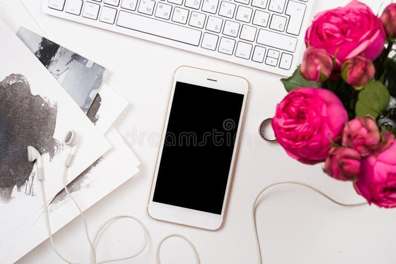 Smartphone, datortangentbord och rosa blommor för fesh på den vita fliken arkivfoto