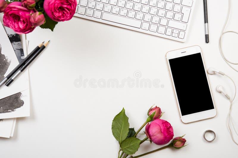 Smartphone, datortangentbord och rosa blommor för fesh på den vita fliken royaltyfri fotografi