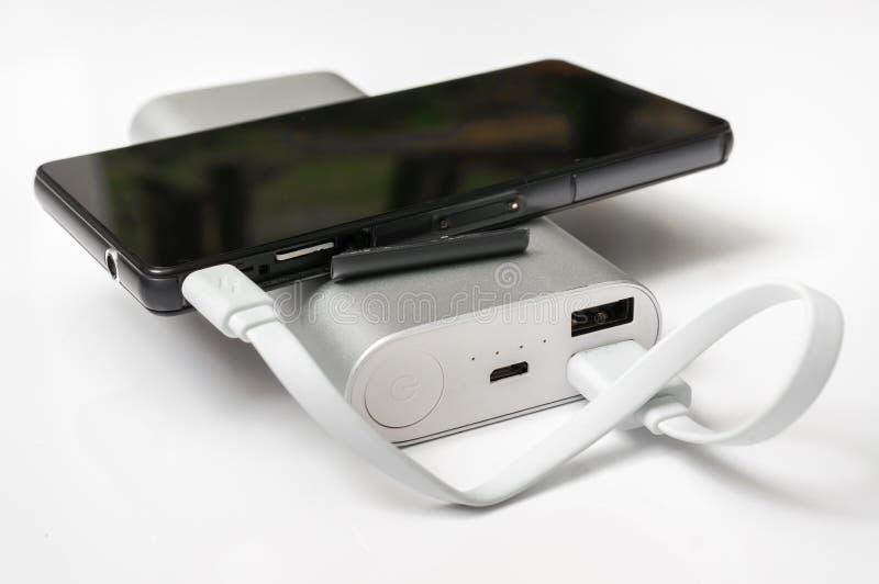 Smartphone de carga del banco blanco del poder fotografía de archivo