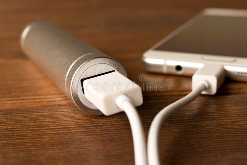 Smartphone de carga del banco de plata del poder en la tabla de madera foto de archivo