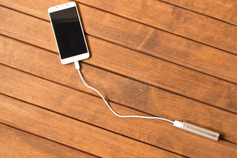 Smartphone de carregamento do banco de prata do poder na tabela de madeira fotografia de stock royalty free